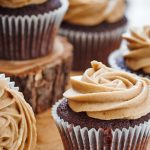 Chocolate cupcakes topped with peanut butter frosting arranged on wooden slabs.