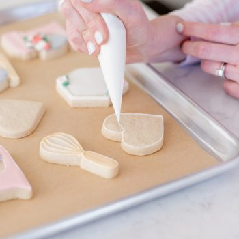 A tray of sugar cookies being icing by a lady holding a pipping bag with white royal icing.