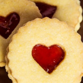 Three Jammie Dodgers biscuits (sandwiched) with a heart cut out in the middle and red jam showing where the cut out is. They are placed on a brown plate.