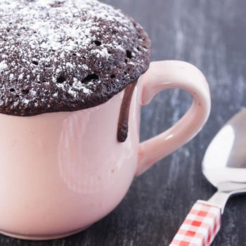 A small pale pink mug with a muffin top chocolate cake popping out it's top with a small drip on the righ hand side next to the handle. The cake is sprinkled with icing sugar. Next to the mug is a teaspoon with a gingham patterned pink handle.