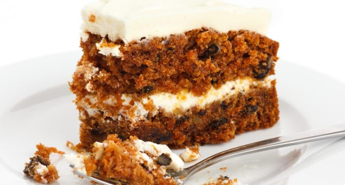 A white plate with a slice of carrot cake with frosting in the middle and on top. A fork has taken a piece of the cake and is resting in front of the cake.
