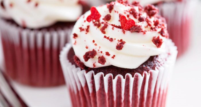 A red velvet cupcake with white cream cheese frosting and crumbs sprinkled on top of the frosting as well as red sugar heart sprinkles.