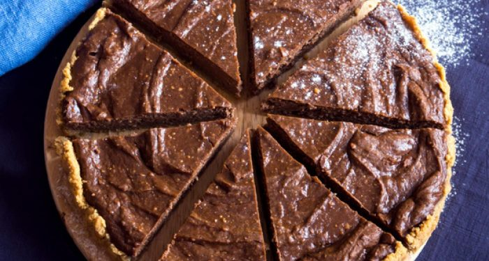 A chocolate cheesecake from and aerial view cut into 8 pieces slightly pulled apart from each other but still in a circular shape.