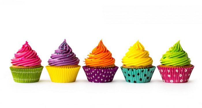 Five frosted cupcakes lined up next to eachother all in different coloured cases  infront of a white background.
